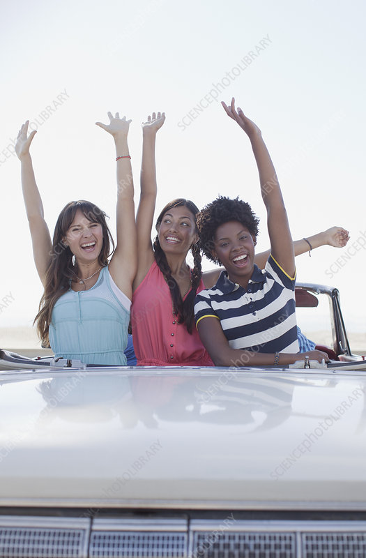 Smiling women cheering in convertible