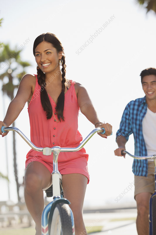 Smiling couple riding bicycles together