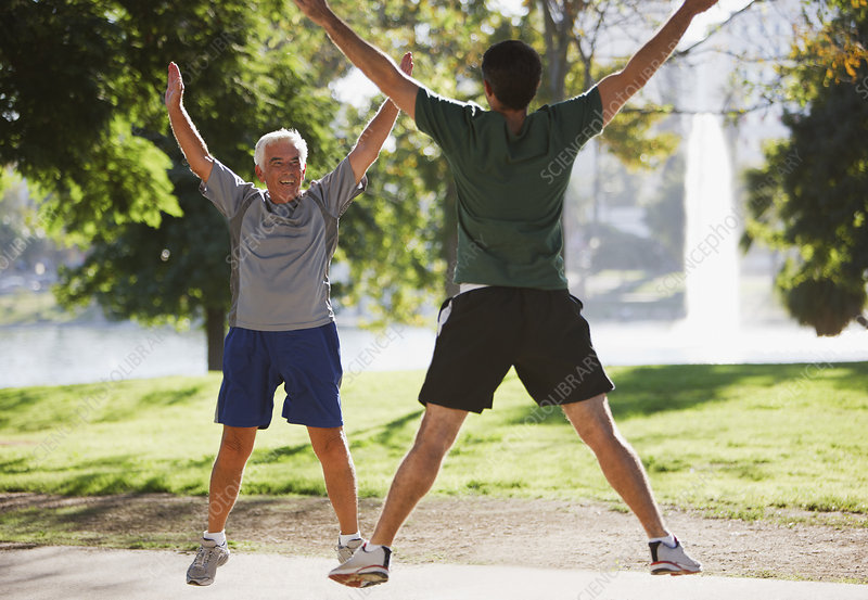 Older men doing jumping jacks outdoors