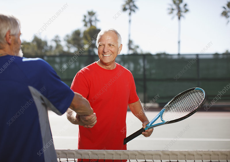 Older men shaking hands on tennis court