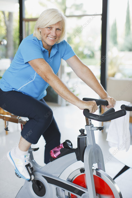 Older woman riding exercise bike in home