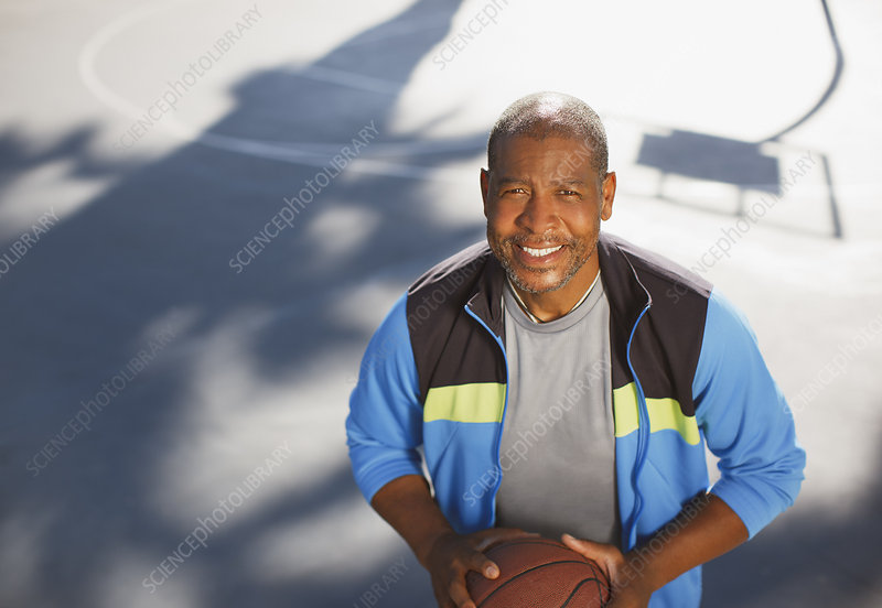 Older man playing basketball on court
