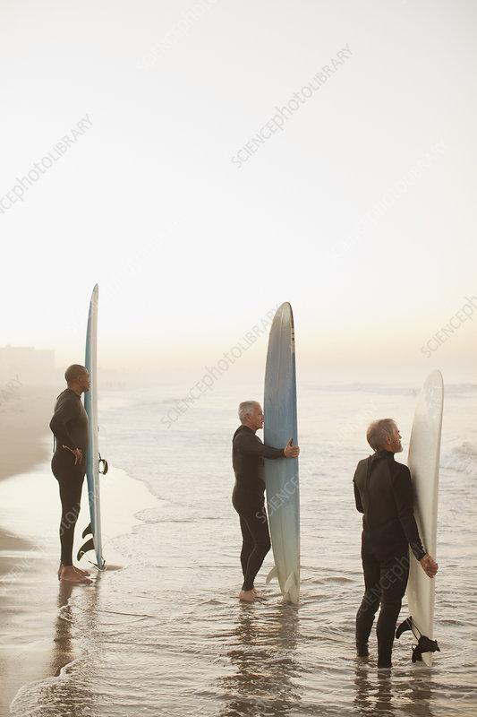 Older surfers holding boards on beach