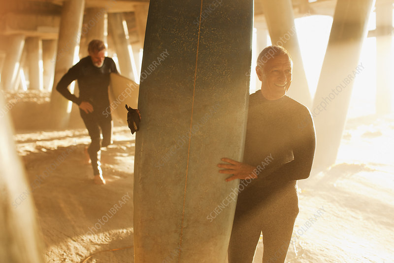 Older surfers carrying boards under pier