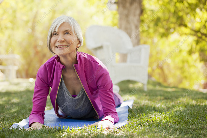 Older woman practicing yoga in backyard