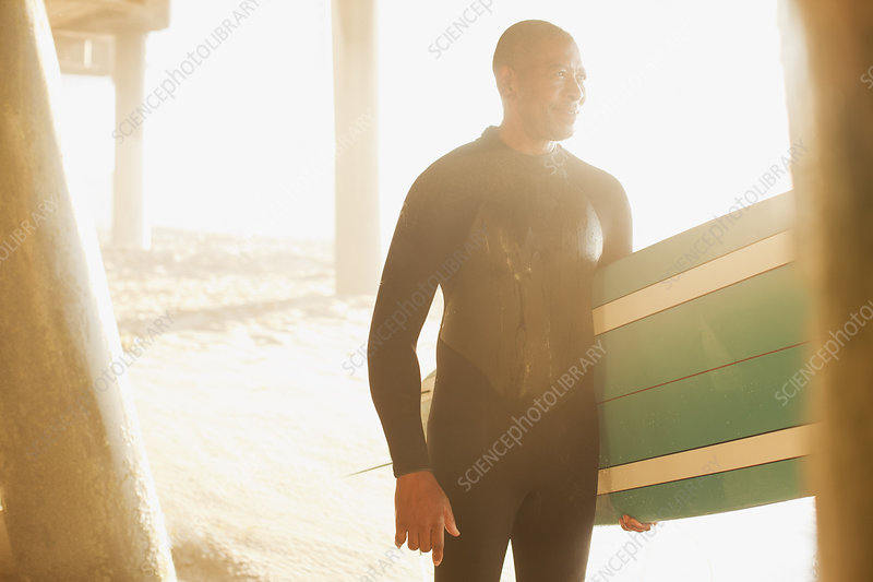 Older surfer carrying board under pier