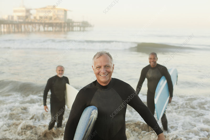 Older surfers carrying boards on beach