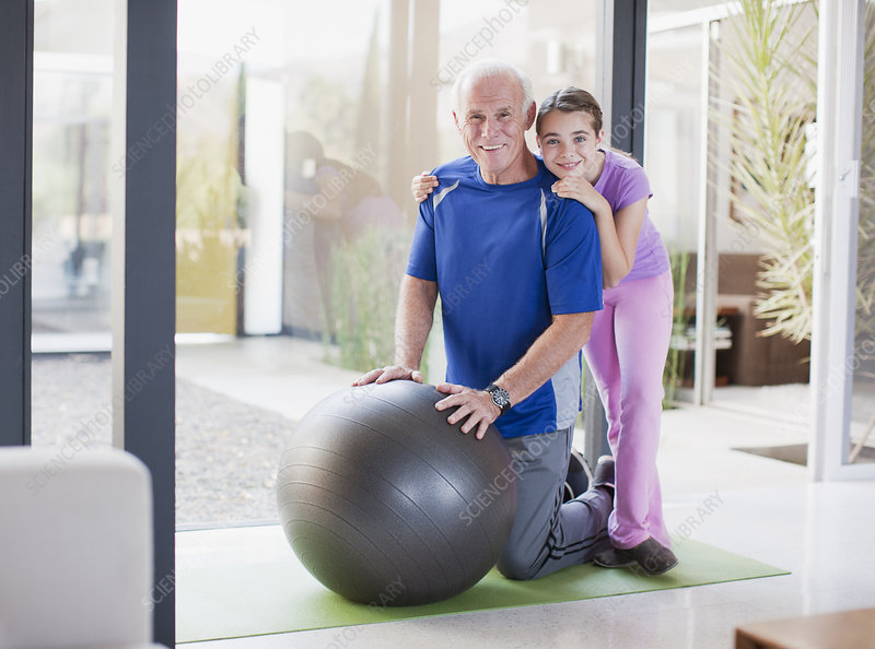 Girl hugging grandfather on exercise ball