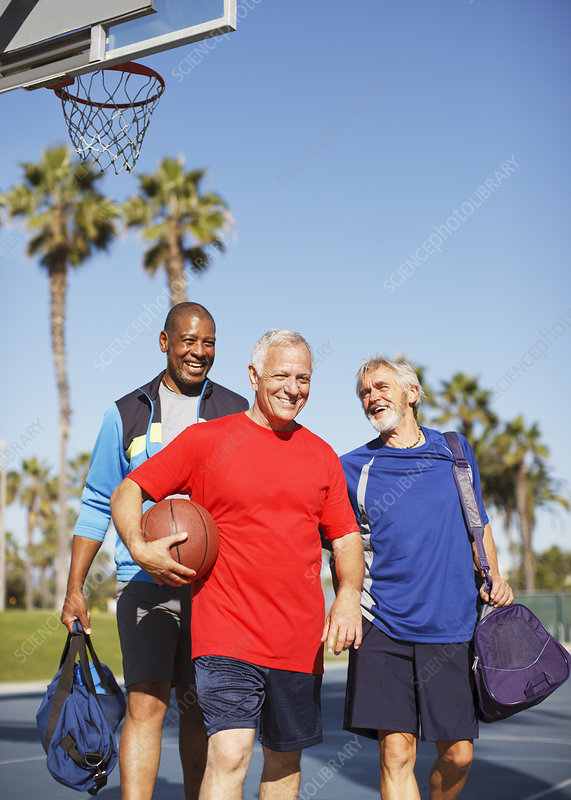 Older men playing basketball on court