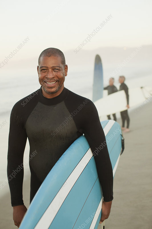 Older surfer carrying board on beach