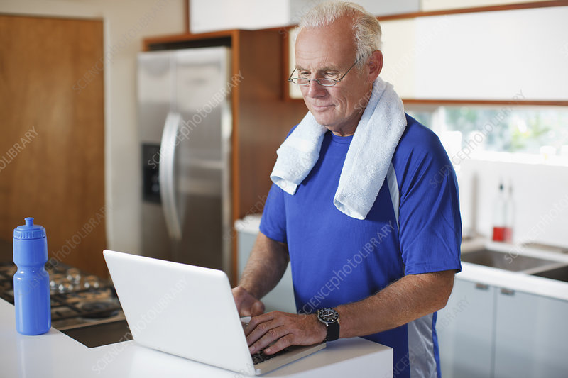 Older man using laptop after workout