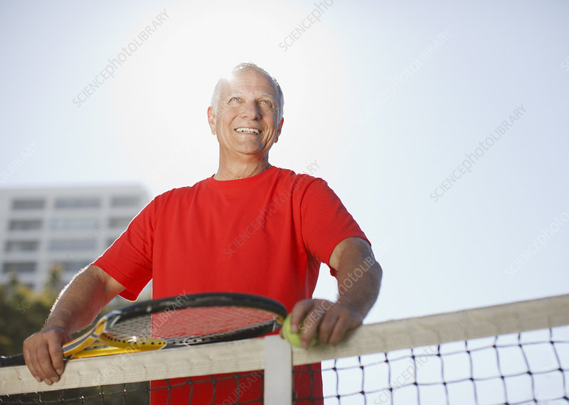Older man playing tennis on court