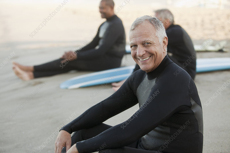 Older surfers sitting on boards on beach