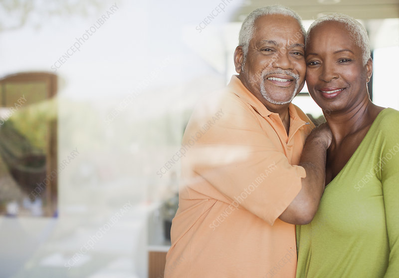 Older couple smiling by window