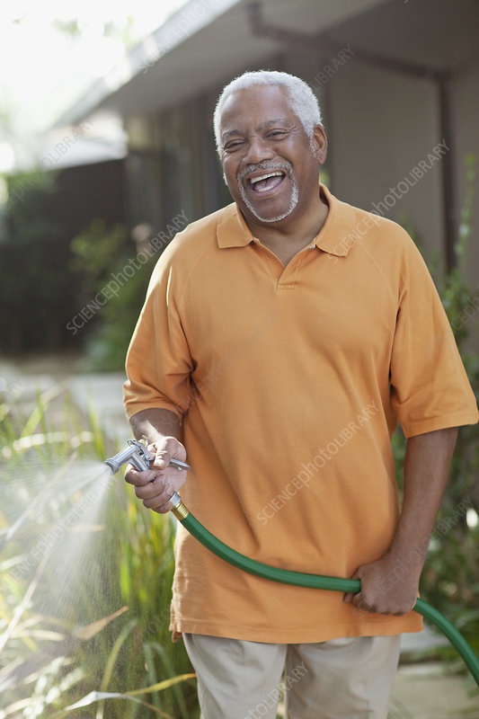 Older men watering plants in backyard