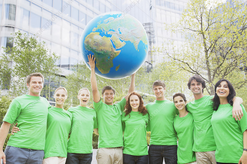 Team in green t-shirts lifting globe