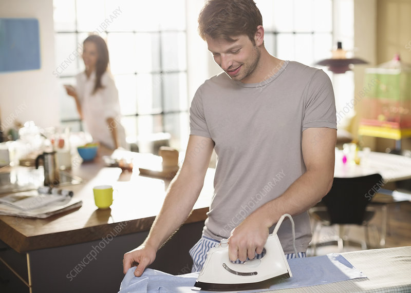 Man ironing shirt in kitchen