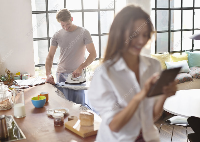 Woman using tablet as boyfriend irons