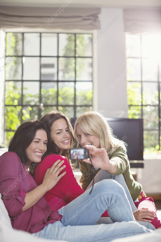 Women taking pictures together on sofa