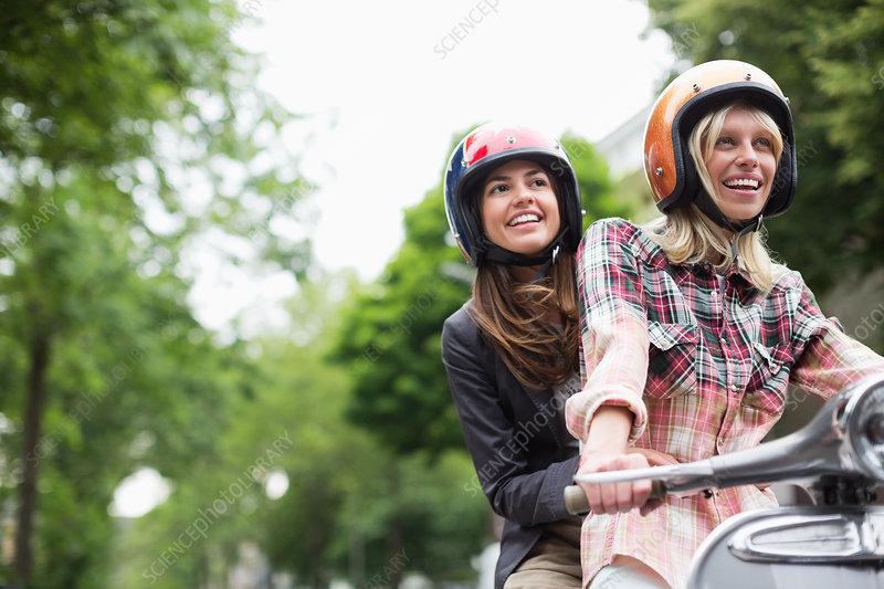 Women riding on scooter together