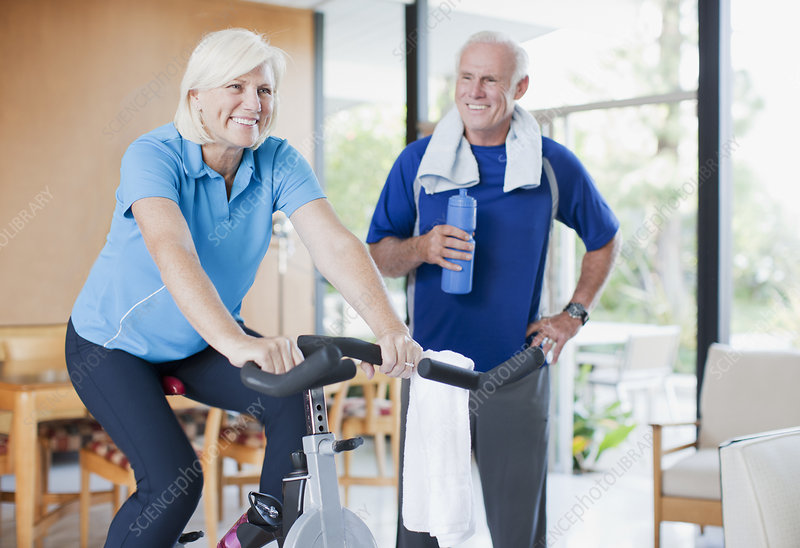 Older woman riding exercise bike at home