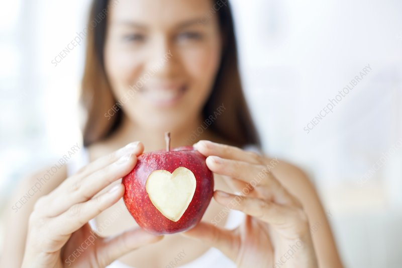 Young woman holding apple with heart