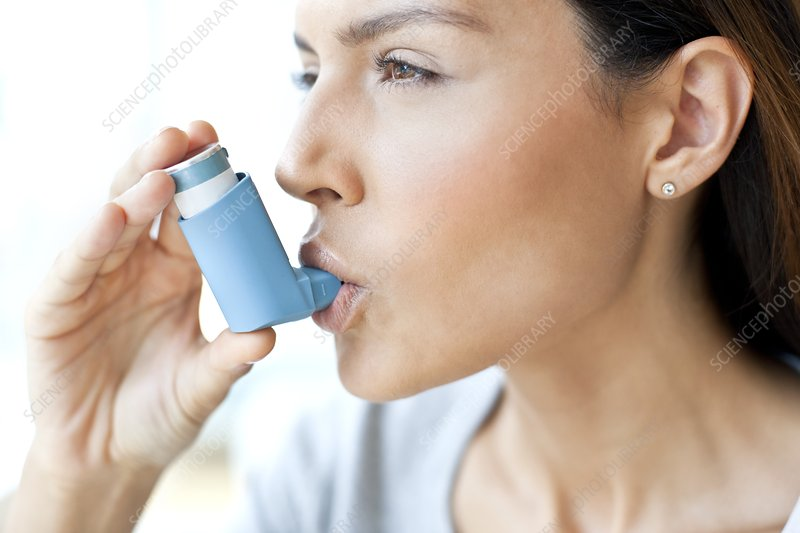 Young woman using inhaler