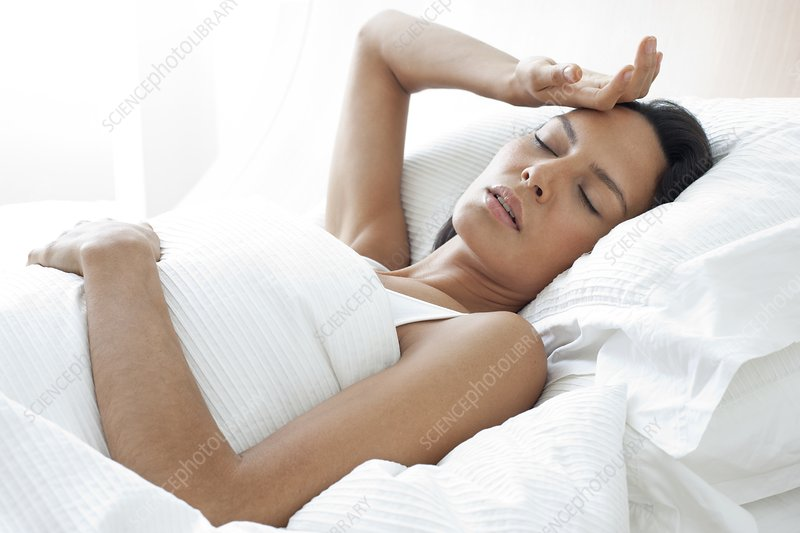 Young woman in bed with hand on forehead