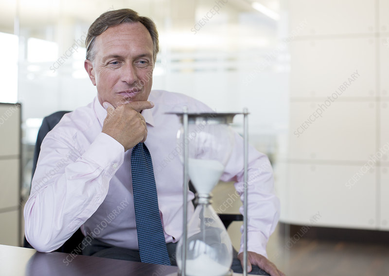 Businessman watching hourglass in office
