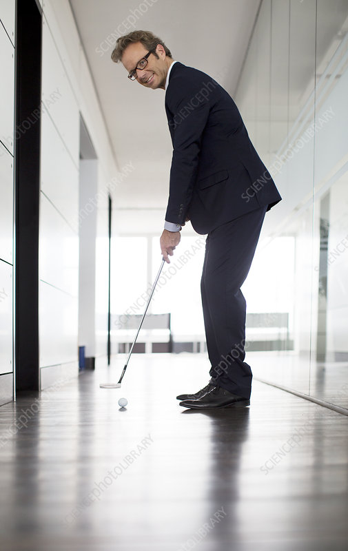 Businessman putting golf ball in office