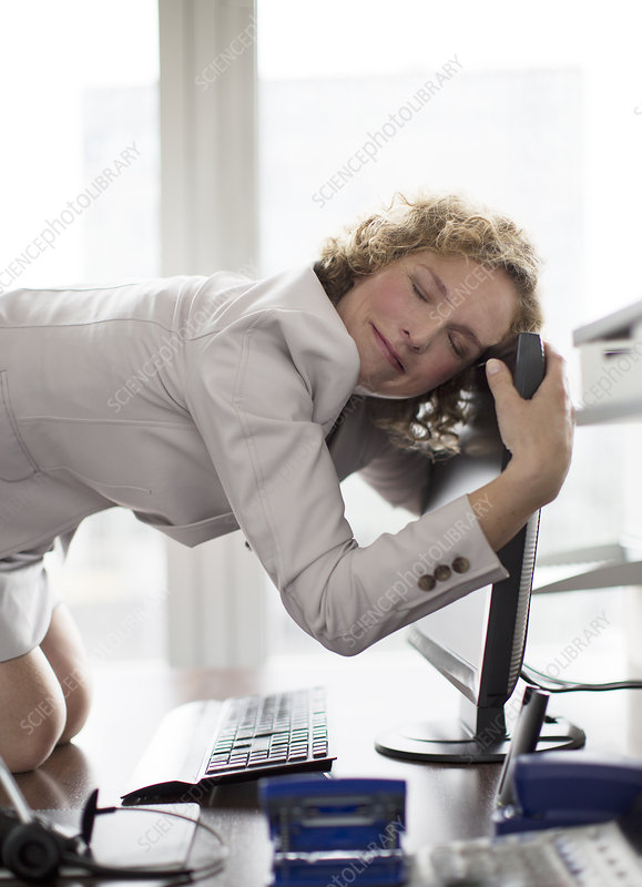Businesswoman hugging computer at desk