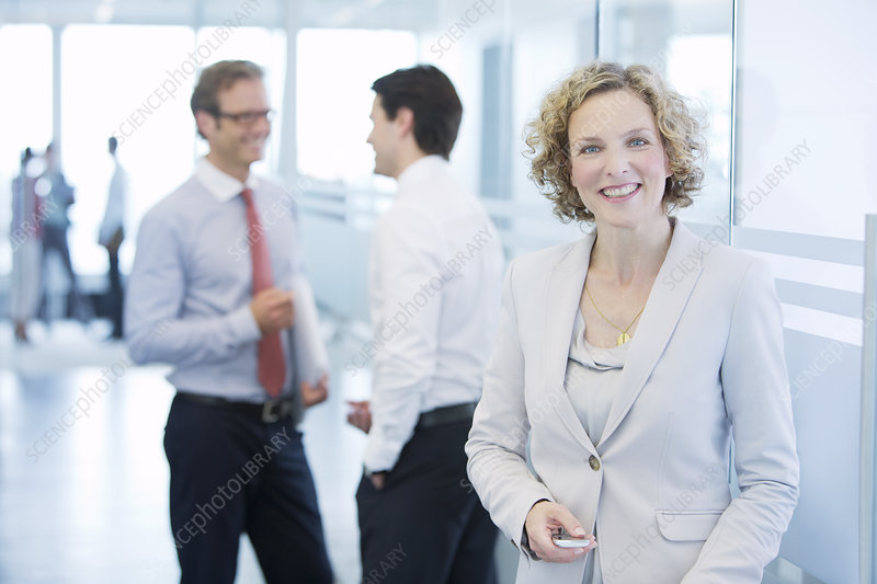 Businesswoman smiling in office hallway