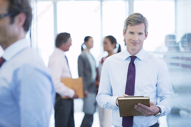 Businessman smiling in office hallway
