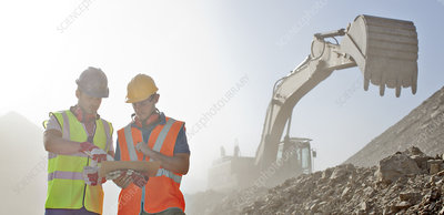 Workers reading blueprints in quarry