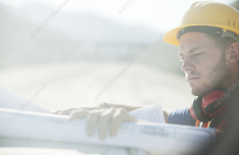 Worker reading blueprints on site