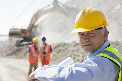 Businessman wearing hard hat in quarry