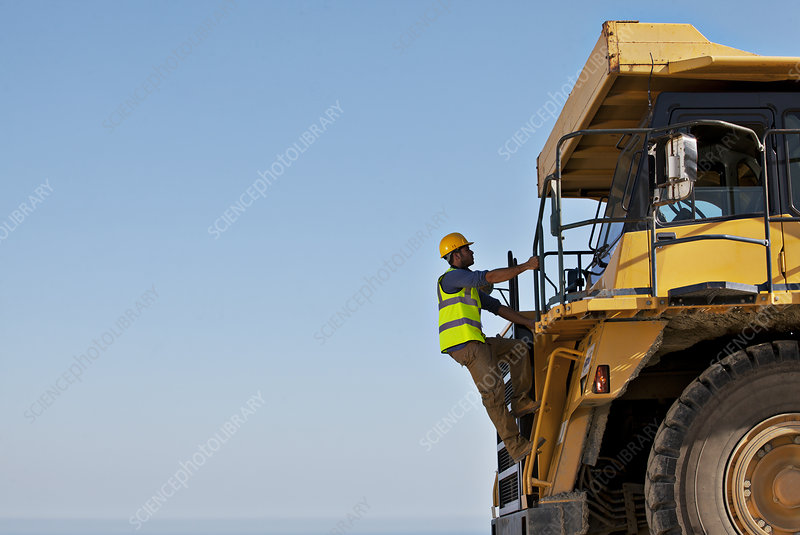 Worker climbing machinery on site