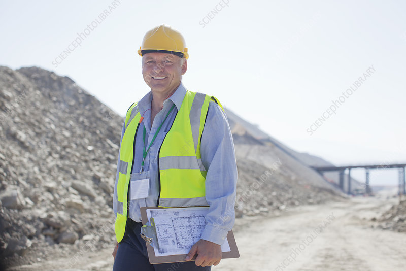 Businessman carrying clipboard in quarry