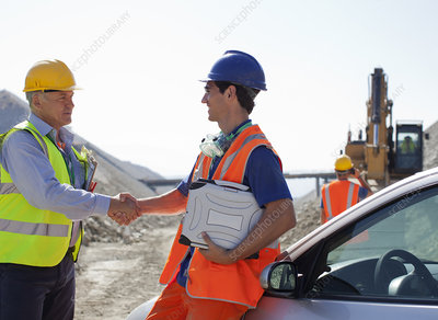 Worker and businessman shaking hands