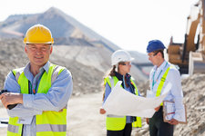 Businessman in hard hat smiling in quarry