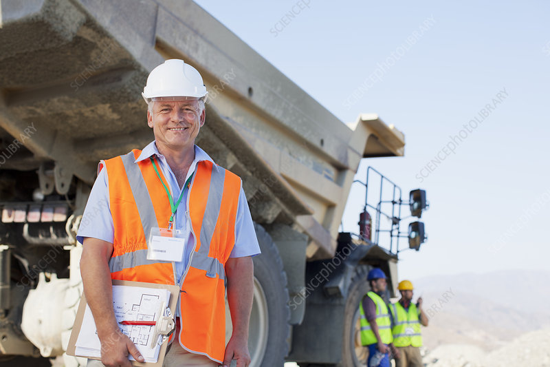 Businessman standing by truck on site