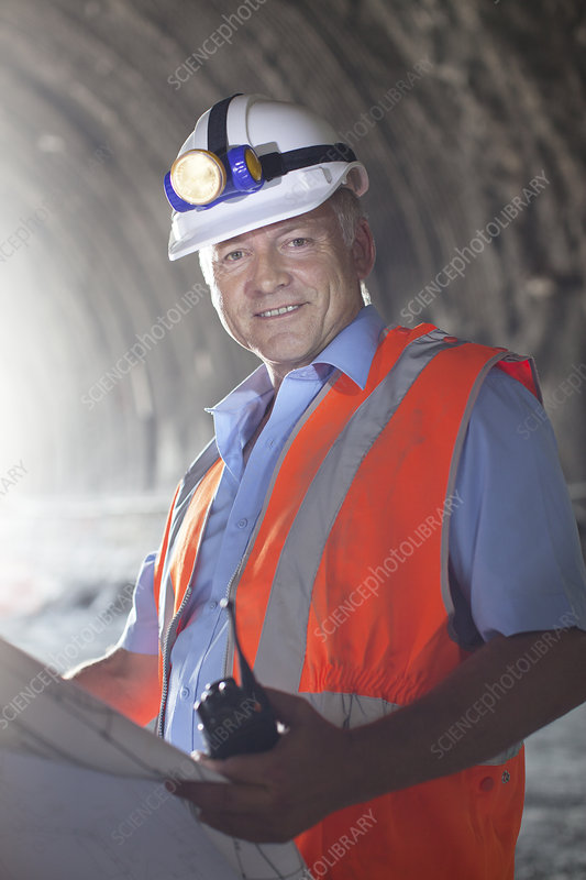 Businessman reading blueprints in tunnel