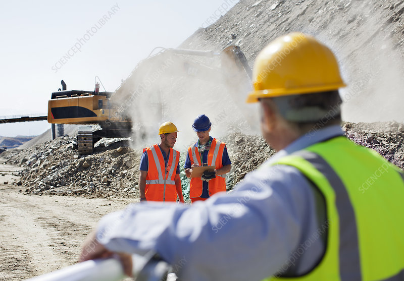 Businessman watching workers in quarry