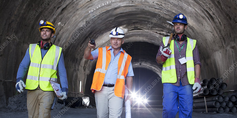 Businessman and workers walking in tunnel