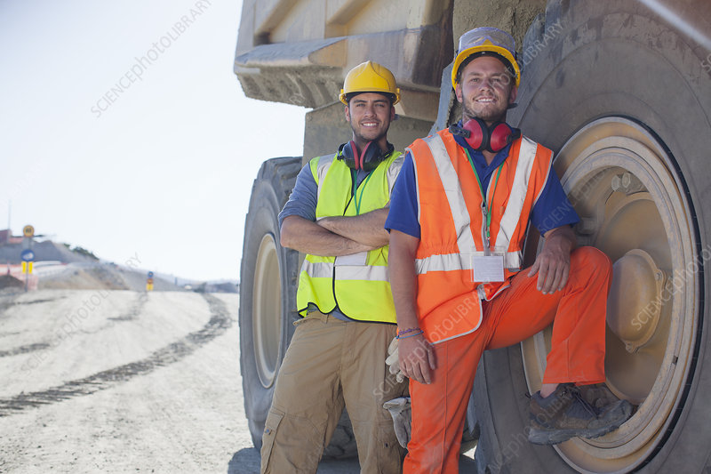 Workers leaning on machinery on site