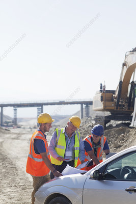 Businessman and workers talking in quarry