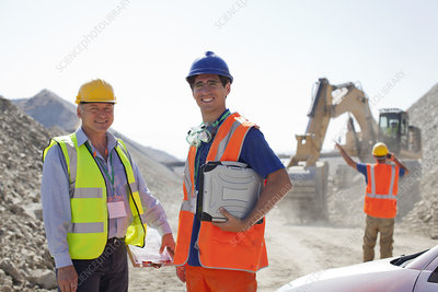 Worker and businessman standing in quarry