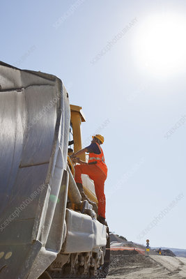 Worker climbing machinery in quarry