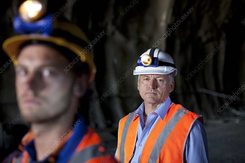 Businessman and worker standing in tunnel