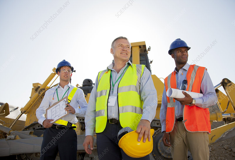 Businessmen in hard hats standing on site
